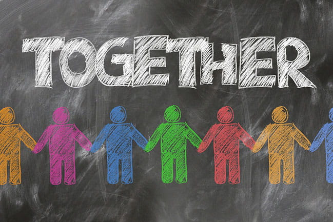the word together written on a chalk board with multicolored stick figures holding hands below