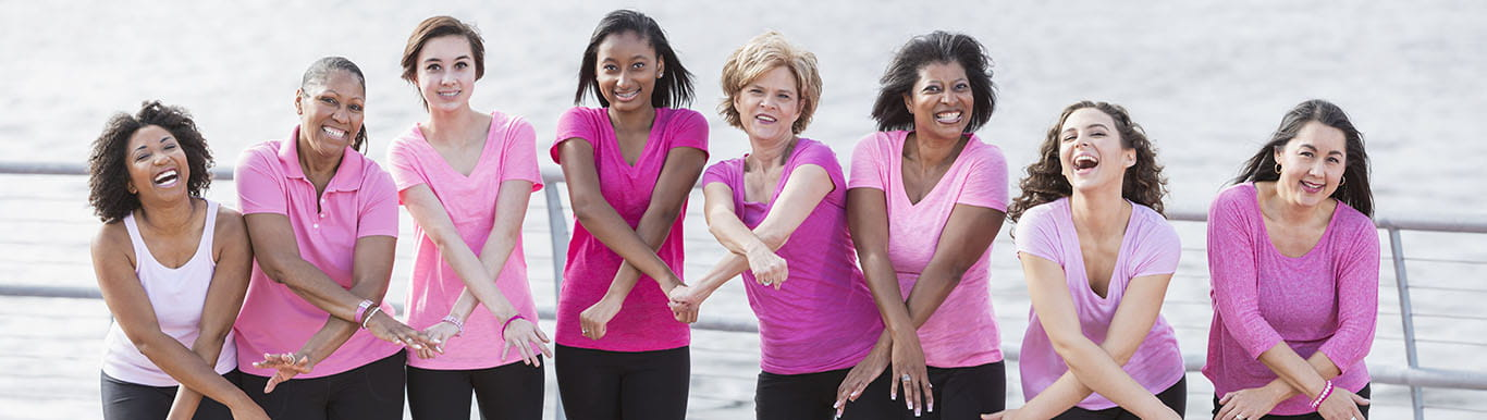 group of women wearing pink shirts cross their arms at the wrist to represent the cancer awareness ribbon