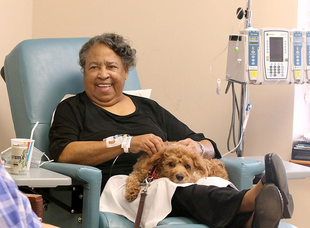 Rosalind Rivers pets one of MUSC's pet therapy dogs