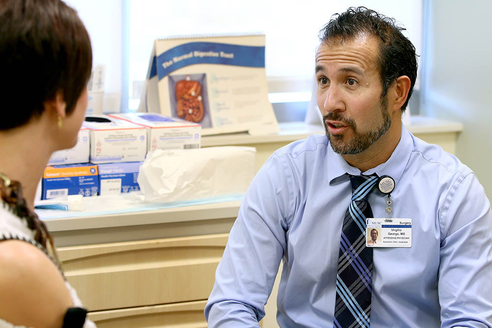 Virgilio George, M.D., talks with a patient