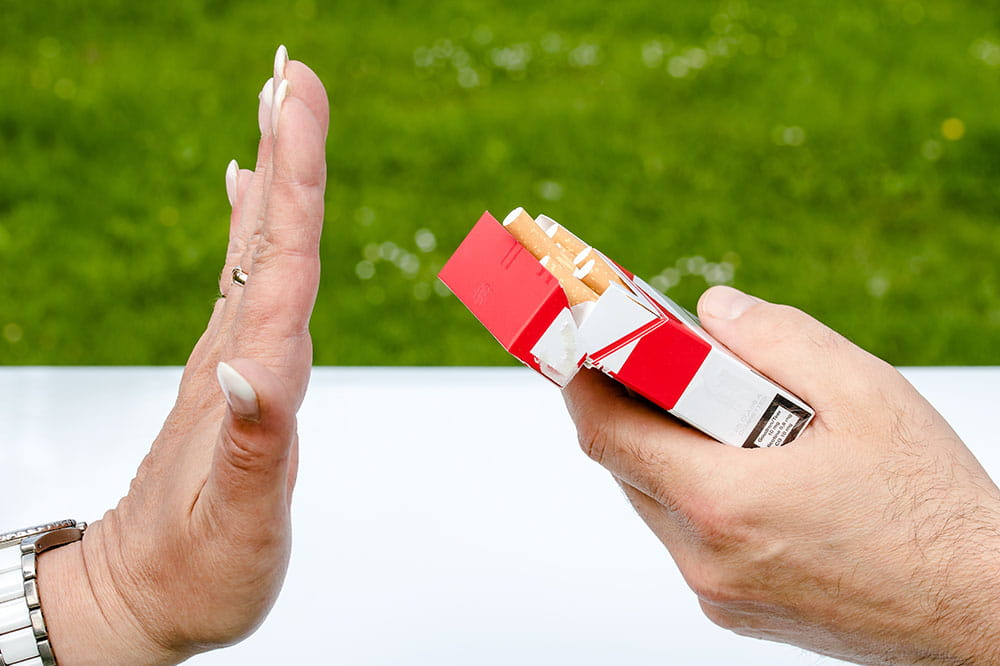 A hand rejects another hand holding an open pack of cigarettes