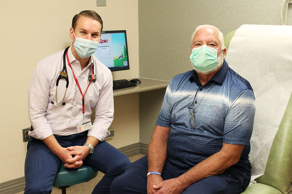 Dr. Brian Greenwell and Samuel Jackson sit in an exam room with masks on
