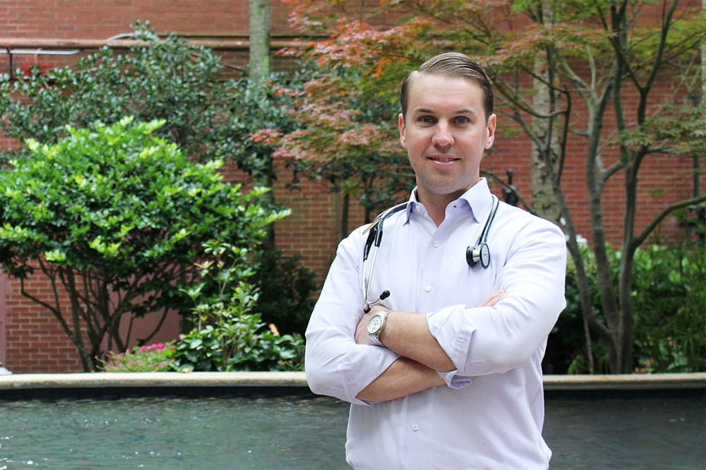 Dr. Brian Greenwell stands outside in a garden with a stethoscope around his neck