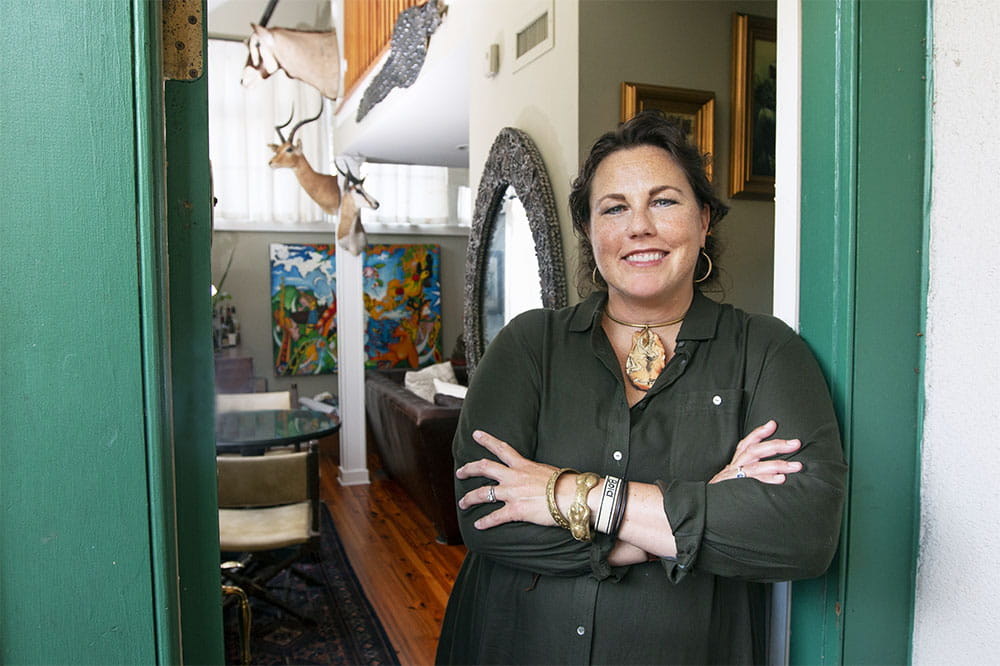 Suzette Bussey stands in a doorway in her house with art and furniture behind her