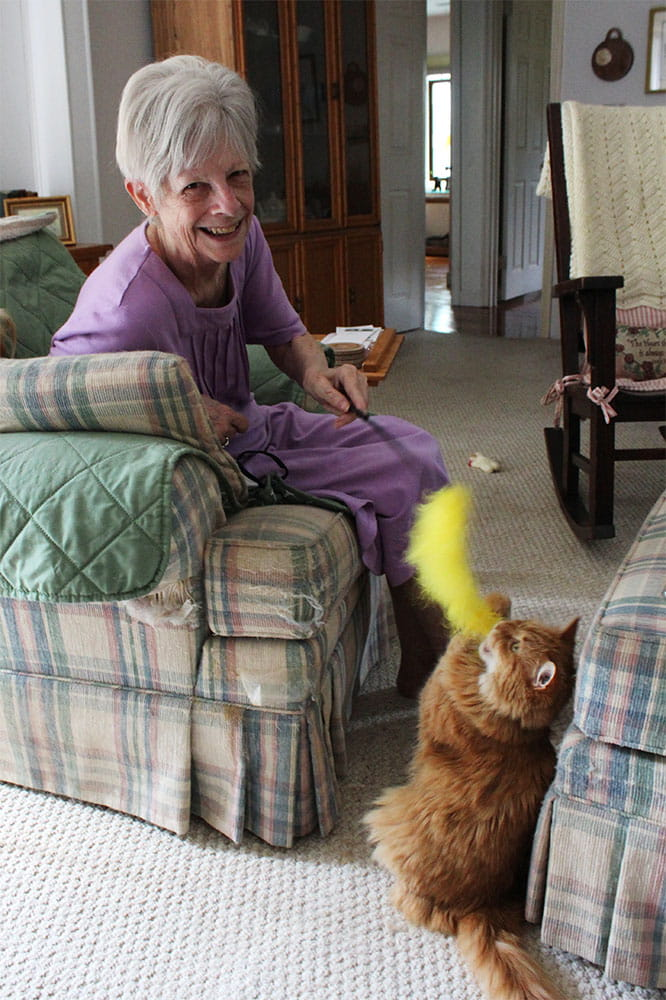 Janet Smith plays with her cat Moe