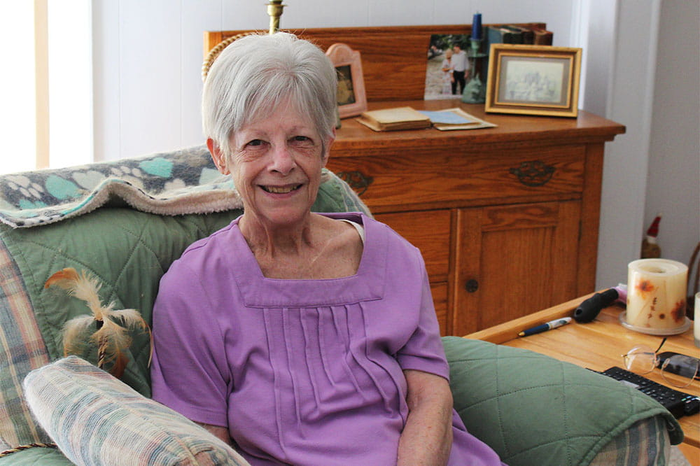 Janet Smith sits in her home