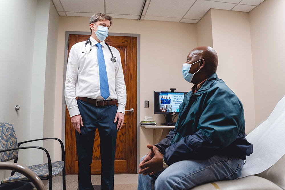 Dr. Todd Gourdin talks with a patient in an exam room while both wear masks
