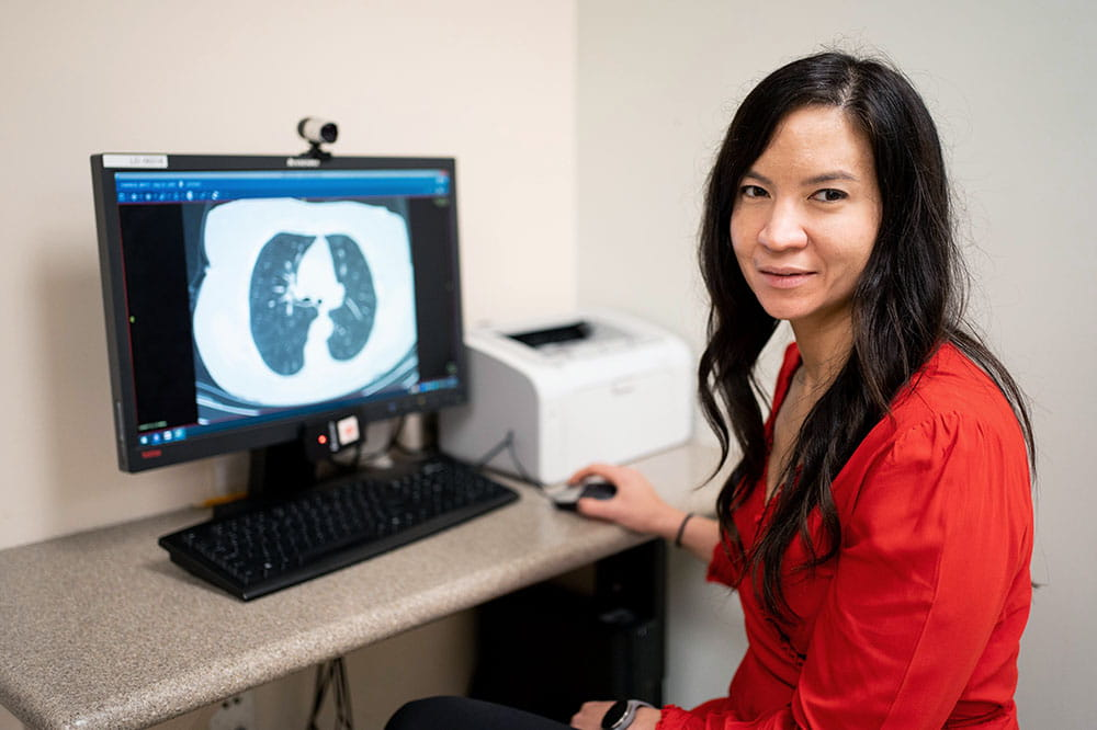 Dr. Nichole Tanner sits at a computer showing a lung cancer scan