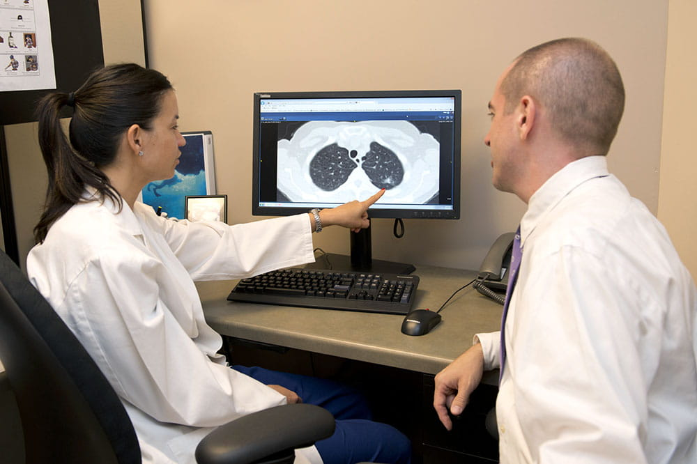 Dr. Nichole Tanner and Dr. Benjamin Toll look at a computer showing a lung cancer scan