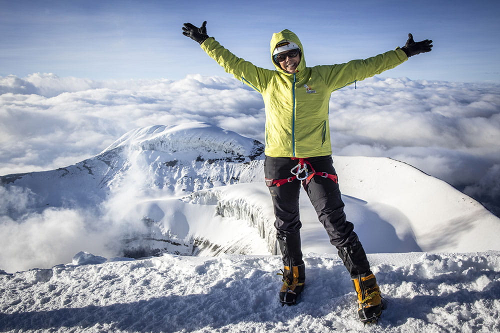Cokie Cox stands on top of a snowy mountain in Ecuador with both arms raised