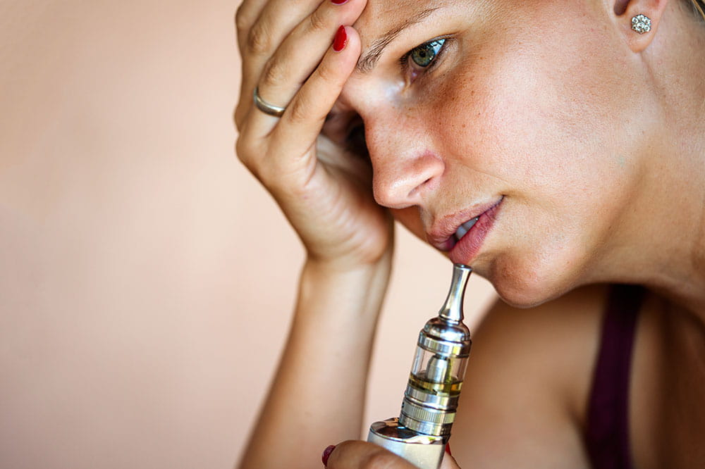 a woman holds an ecigarette while her other hand is on her forehead as she thinks about quitting