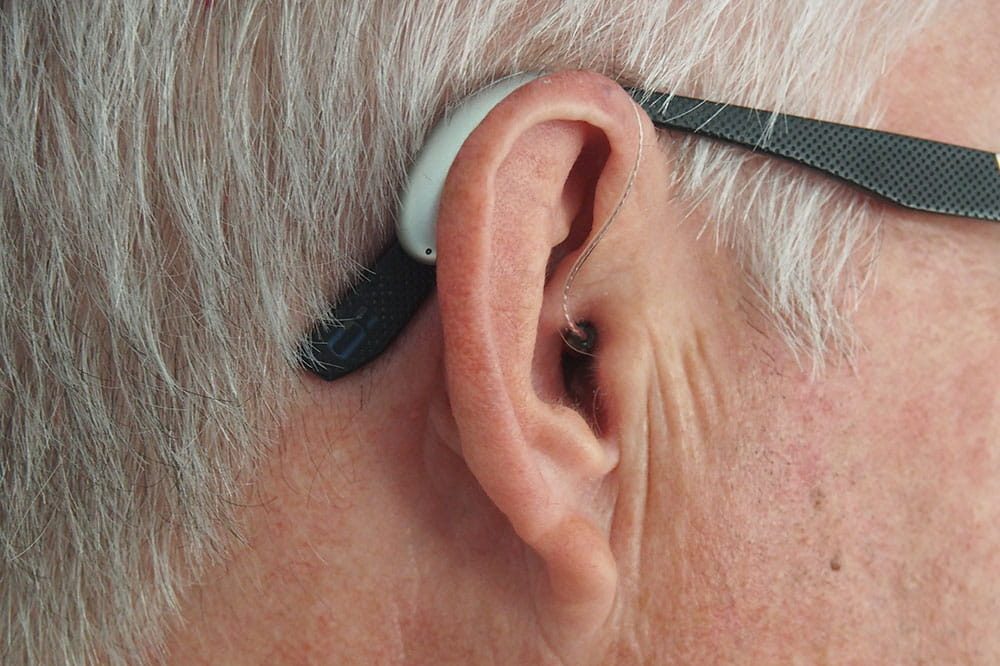 Closeup of a man's ear. He is wearing a hearing aid.